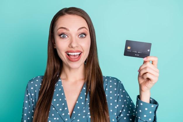 Porträt eines erstaunten positiven mädchens, das eine kreditkarte für den gehaltsgewinn hält, trägt eine blaue bluse einzeln auf türkisfarbenem hintergrund