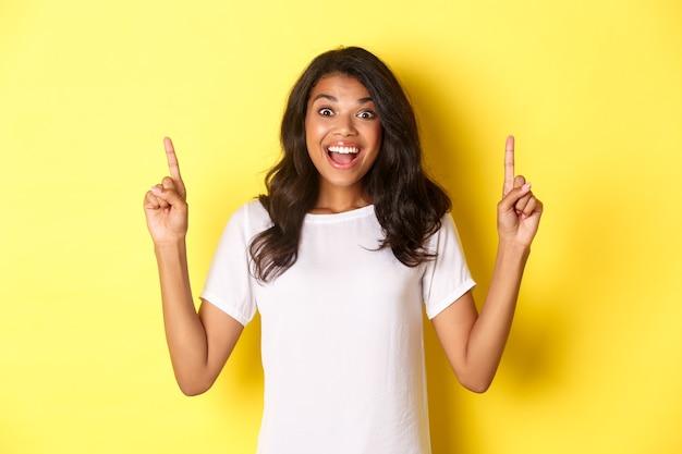 Porträt eines erstaunten, schönen afroamerikanischen mädchens im weißen t-shirt, das auf coole werbung reagiert, mit den fingern nach oben zeigt und auf gelbem hintergrund steht.