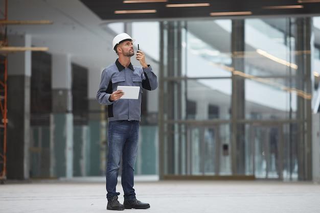 Porträt eines erwachsenen arbeiters in voller länge, der mit einem walkie-talkie spricht, während er die arbeit auf der baustelle oder in einer industriewerkstatt überwacht.
