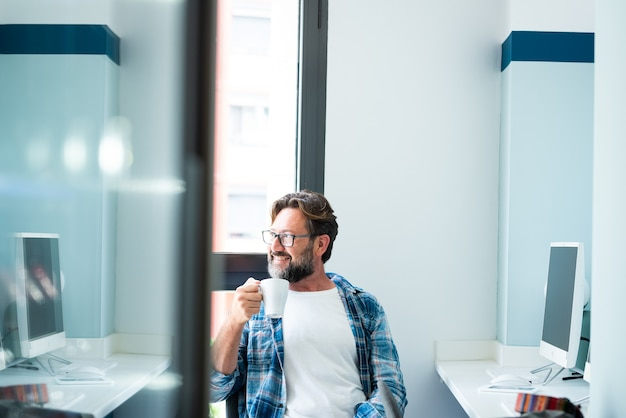 Porträt eines erwachsenen mannes, der im desktop-büro sitzt, eine arbeitspause macht, kaffee trinkt und aus dem fenster schaut - online-lifestyle-aktivität für freiberufliche mitarbeiter - reife kaukasier und computer