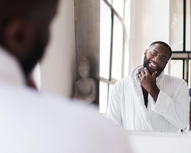 Porträt eines erwachsenen mannes, der sich im spiegel beobachtet
