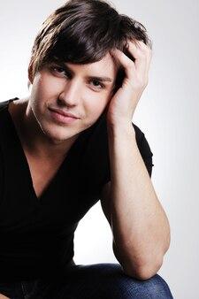 Porträt eines erwachsenen schönheitsmannes, der im studio aufwirft. hübscher kerl, der auf dem stuhl sitzt