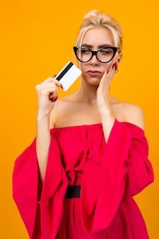 Porträt eines europäischen mädchens in einem roten kleid mit einer kreditkarte mit einer schablone für eine bank auf einem plakat