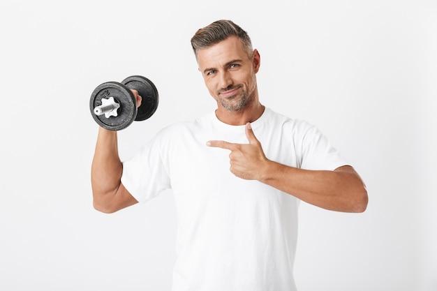 Porträt eines europäischen mannes der 30er jahre mit borsten, der ein lässiges t-shirt trägt, das bizeps pumpt und die hantel einzeln auf weiß hebt
