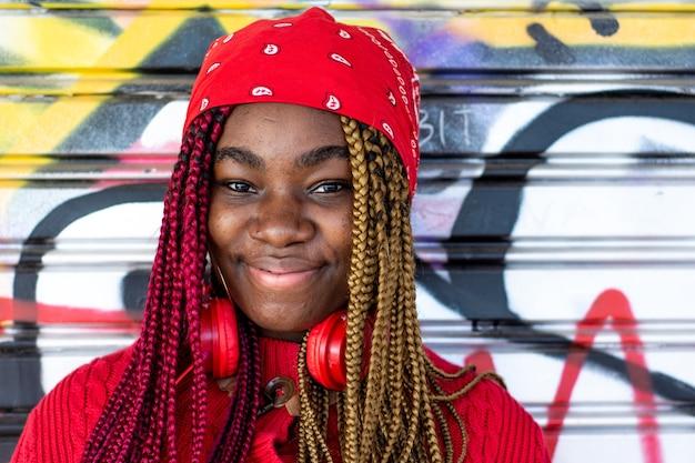 Porträt eines exotischen schwarzen mädchens mit farbigen zöpfen. rote kopfhörer hängen am hals. gekleidet in einen roten pullover und ein rotes kopftuch. graffiti-wandhintergrund