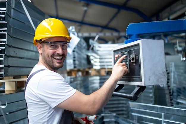Porträt eines fabrikarbeiters, der eine industriemaschine bedient und parameter auf dem computer einstellt