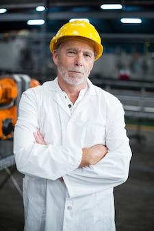 Porträt eines fabrikingenieurs, der mit verschränkten armen steht