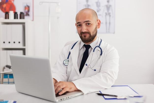 Porträt eines facharztes, der die kamera untersucht, die im konferenzraum arbeitet, um krankheitsexpertise mit laptop-computer zu analysieren. arzt verschreibt pillen medikamente gesundheitsbehandlung
