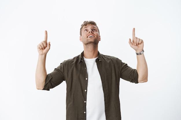 Porträt eines faszinierten und verzauberten, erstaunten, attraktiven blonden kerls mit borstenlächeln, der erfreut den kopf hebt, als er beeindruckt und glücklich aussieht und nach oben über die graue wand zeigt