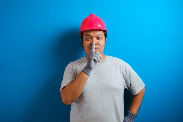Porträt eines fetten asiatischen mannes mit rotem helm, der darum bittet, ruhig zu sein, geste zum schweigen, stillekonzept Premium Fotos