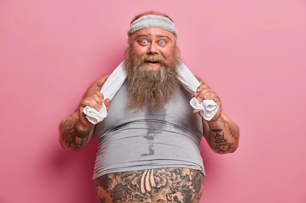 Porträt eines fetten bärtigen mannes mit verschwitztem körper, fühlt sich nach anstrengenden übungen im fitnessstudio müde, hat einen dicken bauch, der aus dem t-shirt herausragt, hält die hände auf dem handtuch, treibt regelmäßig sport, um gewicht zu verlieren