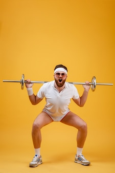Porträt eines fitnessmannes, der übungen mit schwerer langhantel macht