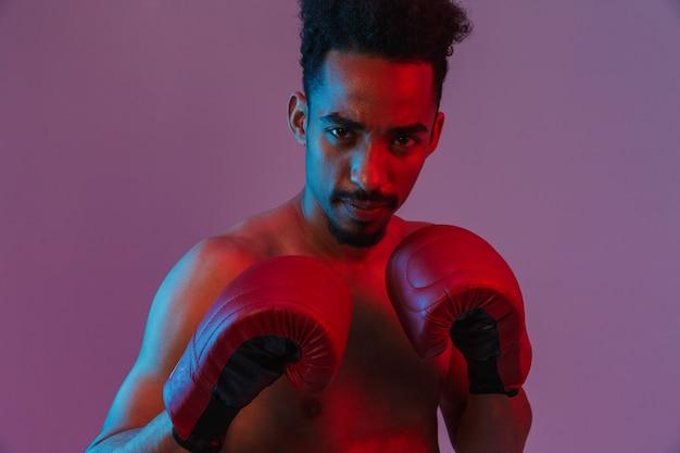 Porträt eines fokussierten hemdlosen afroamerikaners, der in boxhandschuhen posiert, die über einer violetten wand isoliert sind?