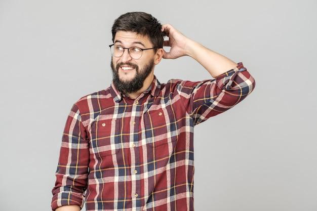 Porträt eines fokussierten intelligenten männlichen modells mit nachdenklich entschlossenem ausdruck