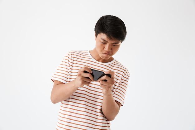 Porträt eines fokussierten jungen asiatischen mannes, der spiele spielt