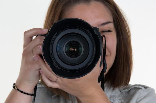 Porträt eines fotografen, der ihr gesicht mit der kamera bedeckt