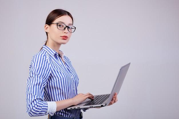 Porträt eines frauenadministrators in einem gestreiften weiß-blauen hemd mit gläsern und einem laptop auf grau. mitarbeiterin des jahres, business lady.