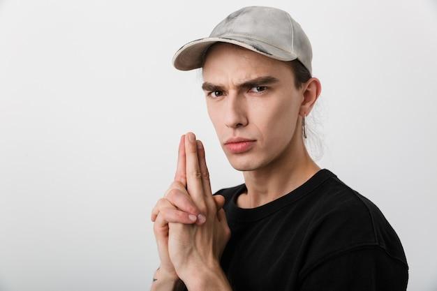 Porträt eines frechen kaukasischen mannes in schwarzer kleidung, der mit den gewehrfingern und auf weiß gestikuliert