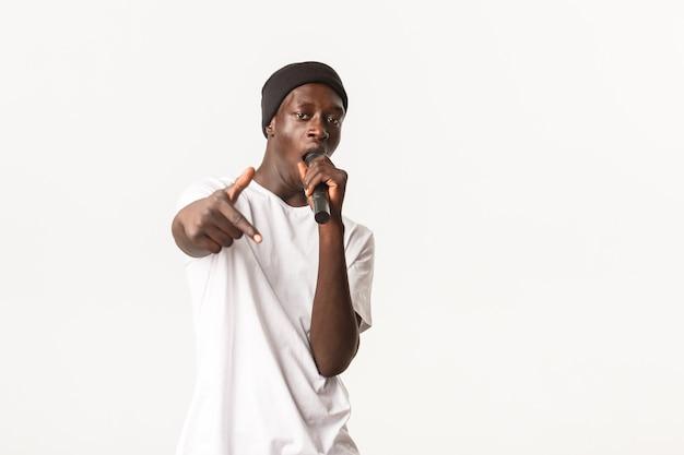 Porträt eines frechen und coolen schwarzen rapper in mütze, der ins mikrofon singt und eine hip-hop-geste macht