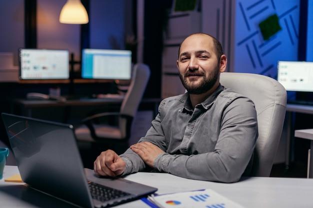 Porträt eines freiberuflers, der die kamera am schreibtisch mit diagrammen betrachtet. kluger geschäftsmann, der im laufe der späten nachtstunden an seinem arbeitsplatz sitzt und seine arbeit macht.