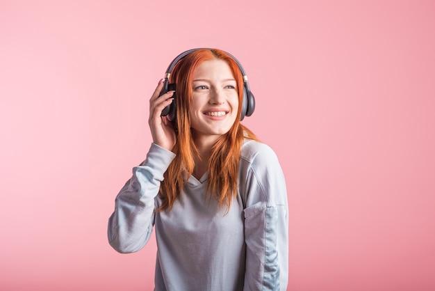 Porträt eines freudigen rothaarigen mädchens, das musik auf kopfhörern im studio auf einem rosa hintergrund hört