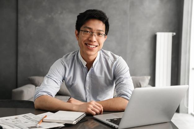 Porträt eines freundlichen jungen asiatischen mannes unter verwendung des laptops
