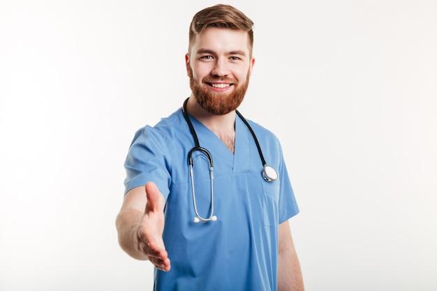 Porträt eines freundlichen lächelnden arztes, der hand für händedruck streckt
