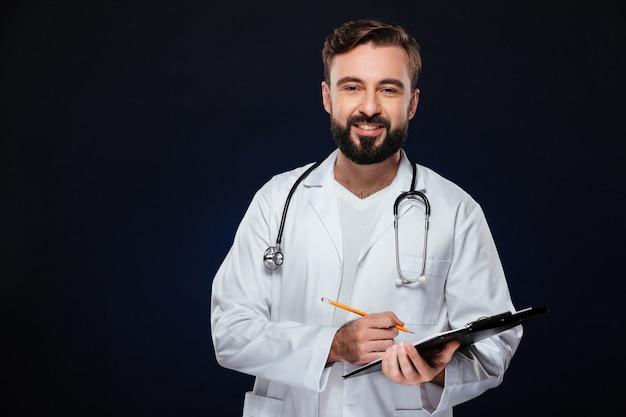 Porträt eines freundlichen männlichen doktors kleidete in der uniform an