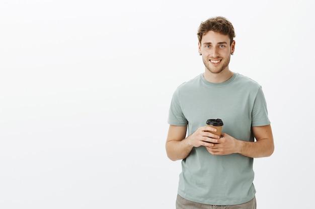 Porträt eines freundlichen, selbstbewussten jungen unternehmers mit blonden haaren und ohrringen, der eine tasse kaffee hält und freudig lächelt, während er beiläufig mit einem kollegen spricht