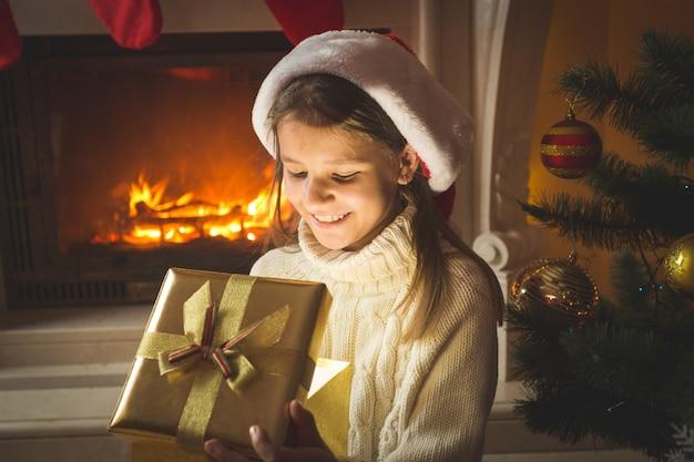 Porträt eines fröhlichen 10 jahre alten mädchens, das in eine magische leuchtende weihnachtsgeschenkbox schaut