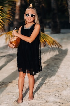 Porträt eines fröhlichen 9-jährigen mädchens mit einem kokosnusscocktail auf dem hintergrund von palmen an einem exotischen strand. kleines mädchen mit einer kokosnuss am strand der insel mauritius.