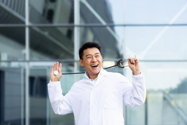 Porträt eines fröhlichen asiatischen arztmannes, der glücklich mit den ergebnissen der arbeit tanzt, die vor dem hintergrund einer modernen klinik draußen geleistet wurde