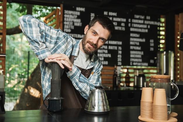 Porträt eines fröhlichen barista-mannes mit schürze, der kaffee macht, während er im straßencafé oder café im freien arbeitet