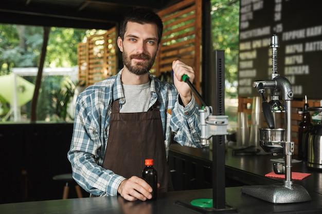 Porträt eines fröhlichen barista-mannes mit schürze, der kaffee macht, während er im straßencafé oder kaffeehaus im freien arbeitet?