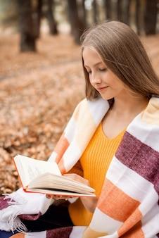 Porträt eines fröhlichen blonden mädchens, das in einem herbstpark sitzt und ein buch liest