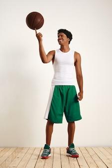 Porträt eines fröhlichen entspannten attraktiven mannes im weißen und grünen basketball-outfit, das einen vintage-lederbasketball auf seinem zeigefinger balanciert