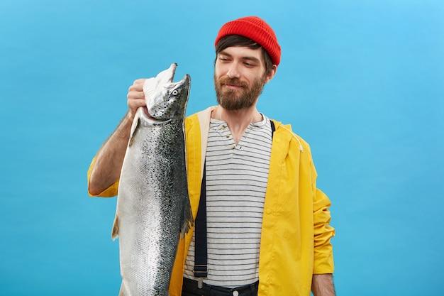 Porträt eines fröhlichen fischers, der einen roten hut, eine gelbe jacke und einen overall trägt und mit erfreutem ausdruck auf seinen fang schaut, der stolz ist.