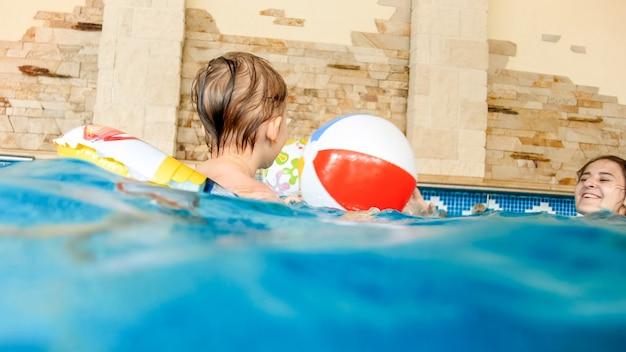 Porträt eines fröhlichen, fröhlichen kleinkindjungen, der mit aufblasbarem wasserball und buntem ring im hallenbad im haus spielt
