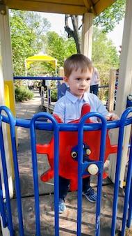 Porträt eines fröhlichen, fröhlichen kleinkindjungen, der vorgibt, ein schiffskapitän auf dem kinderspielplatz im park zu sein und sich drehendes holzlenkrad
