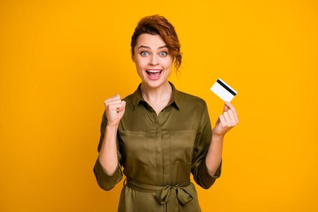 Porträt eines fröhlichen, fröhlichen mädchens, das in den händen eine bankkarte hält, gewinnt glück