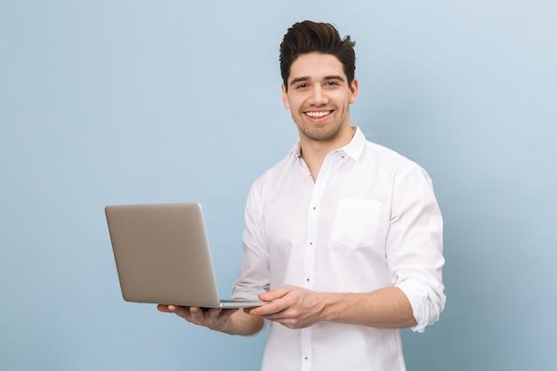 Porträt eines fröhlichen hübschen jungen mannes, der isoliert auf blau steht und am laptop arbeitet