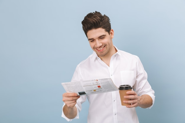 Porträt eines fröhlichen hübschen jungen mannes, der isoliert auf blau steht und kaffeetasse zum mitnehmen hält und zeitung liest