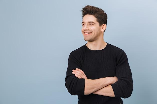 Porträt eines fröhlichen hübschen jungen mannes, der isoliert auf blau steht und wegschaut