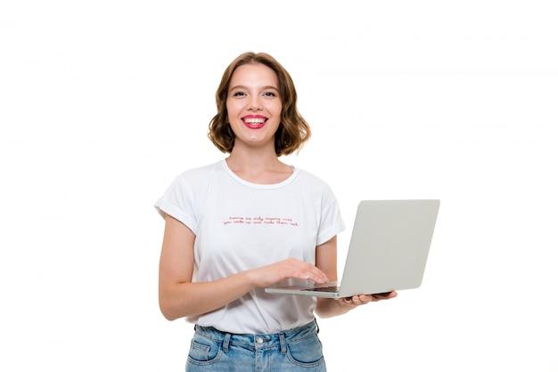 Porträt eines fröhlichen hübschen mädchens, das laptop-computer hält