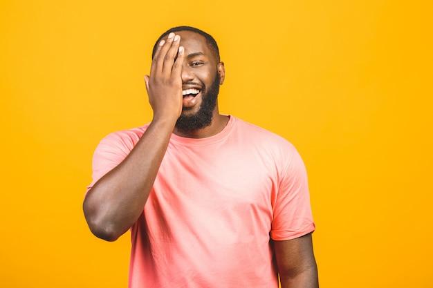 Porträt eines fröhlichen jungen afrikanischen mannes, der gegen gelbe wand steht.