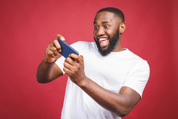 Porträt eines fröhlichen jungen afrikanischen mannes gekleidet in lässigen spielspielen auf handy lokalisiert über rotem hintergrund.