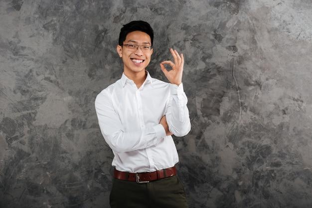 Porträt eines fröhlichen jungen asiatischen mannes im hemd gekleidet