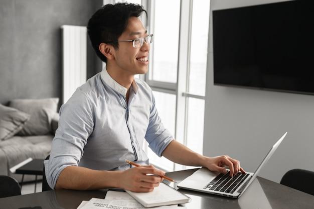 Porträt eines fröhlichen jungen asiatischen mannes unter verwendung des laptops