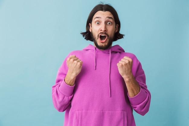 Porträt eines fröhlichen jungen bärtigen brünetten mannes mit hoodie, der isoliert über blauer wand steht und erfolg feiert