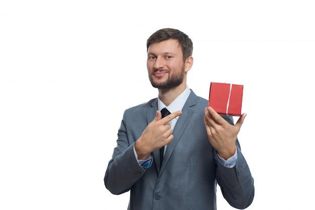 Porträt eines fröhlichen jungen geschäftsmannes in einem anzug, der ein kleines rotes geschenk hält